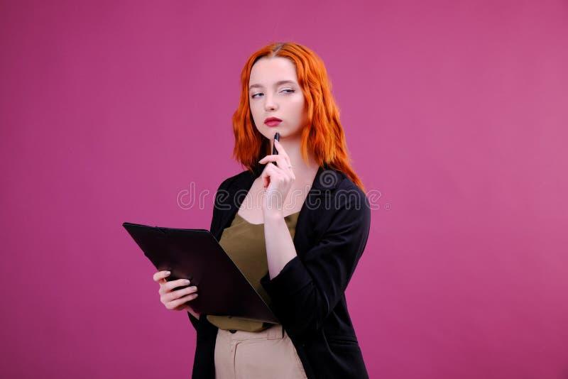 A posi??o bonita consideravelmente nova da mulher, escrita, toma notas, organizador do caderno do livro de texto da terra arrenda fotografia de stock
