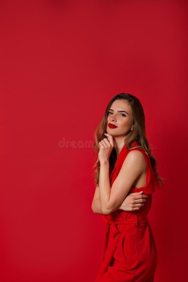 Posi??o branca vestindo alegre da camisa da mulher elegante isolada sobre o fundo bege, guardando a m?o perto da cara imagem de stock