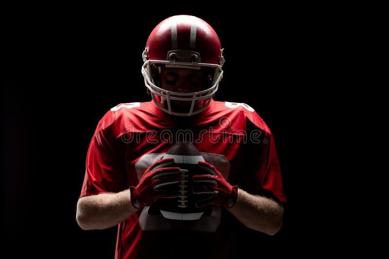 Posi??o do jogador de futebol americano com capacete e bola do rugby imagens de stock royalty free