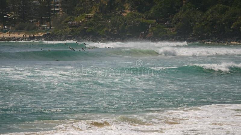 Posibilidad muy remota de las personas que practica surf que montan ondas en el greenmount en el Gold Coast de Queensland fotos de archivo