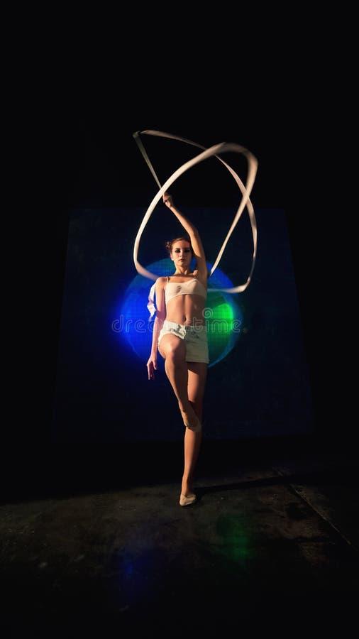 Posibilidad muy remota de un entrenamiento joven atractivo de la mujer del gimnasta con la cinta de la gimnasia imagen de archivo libre de regalías