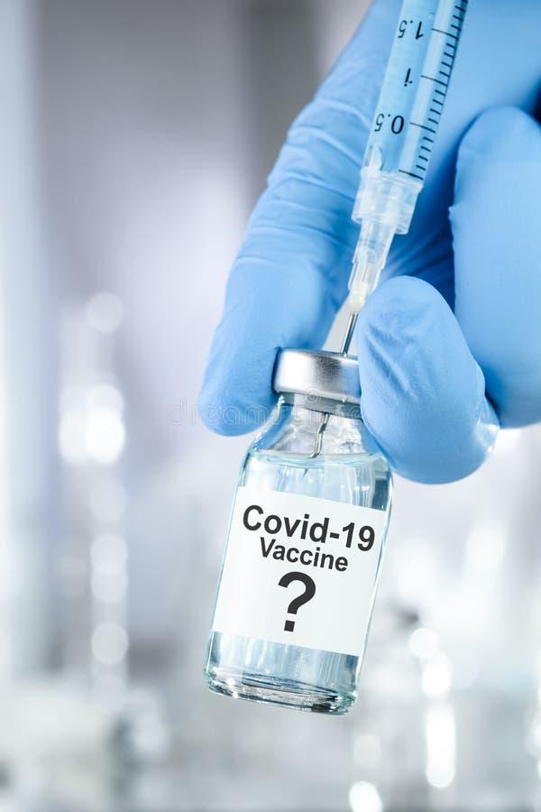 Posible cura con una mano en guantes médicos azules sosteniendo el vial de Coronavirus, virus Covid 19, vacuna fotos de archivo libres de regalías