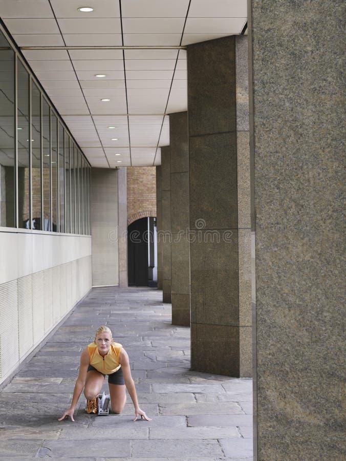 Posición de Crouching In Starting del atleta de sexo femenino en pórtico fotos de archivo