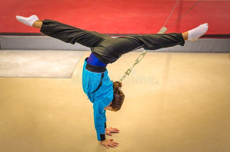 Posición del pino practicante de la muchacha joven del gimnasta imagen de archivo