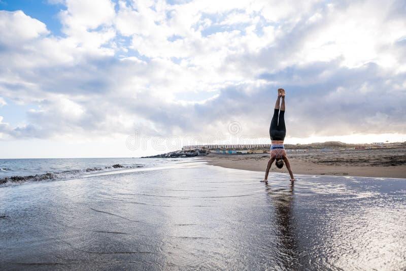 Posición equilibrada dura para la mujer fuerte y deportiva en la playa respecto a la orilla councept de la aptitud y del entrenam foto de archivo libre de regalías