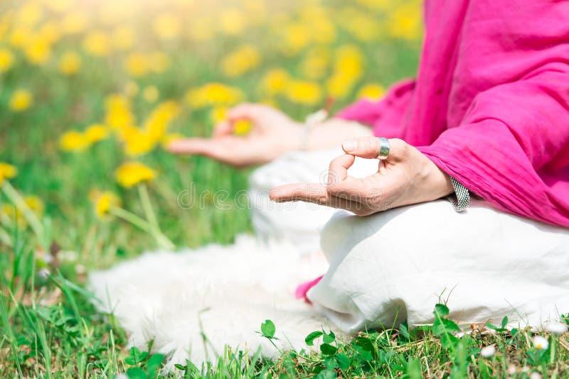 Posicione a prática da ioga ele uma menina na natureza em flores da mola fotografia de stock