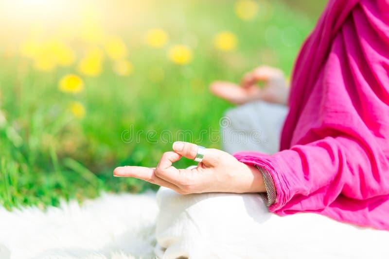 Posicione a prática da ioga ele uma mulher na natureza em flores da mola imagens de stock