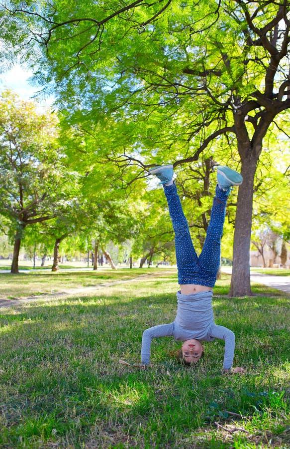 Posiciones del pino de la muchacha del niño al revés en el parque imágenes de archivo libres de regalías