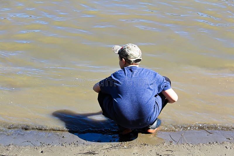 Posiciones en cuclillas jovenes de un muchacho en el borde del agua fotografía de archivo libre de regalías