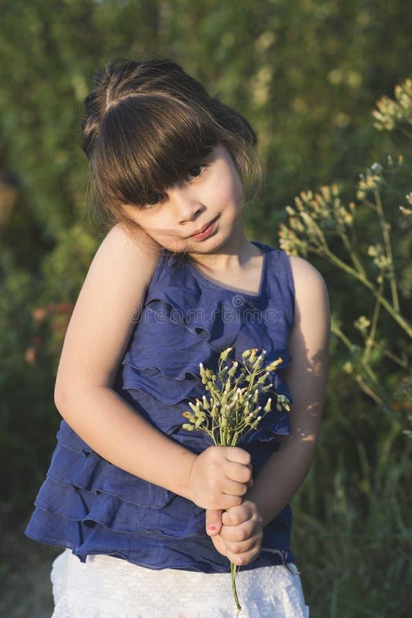 Posig mignon de petite fille au coucher du soleil avec des fleurs photographie stock libre de droits