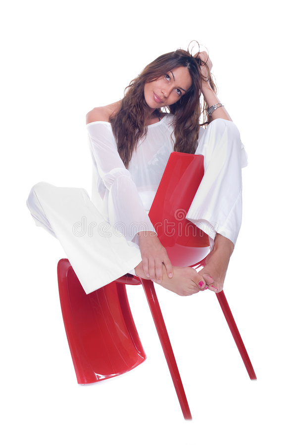 Posing. Beautiful woman sitting on red plastic chair stock photos