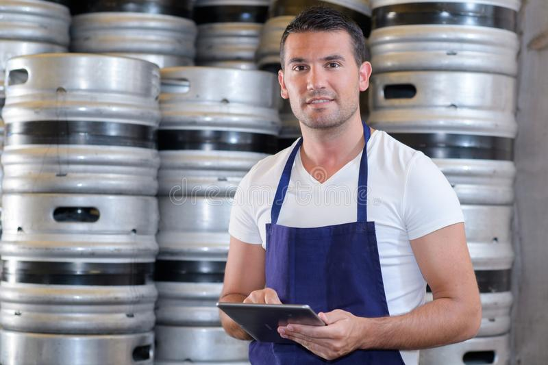 Posing with beer kegs. Warehouse stock photography