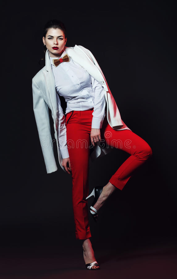 Posing elegant woman in red pants and white coat stock images