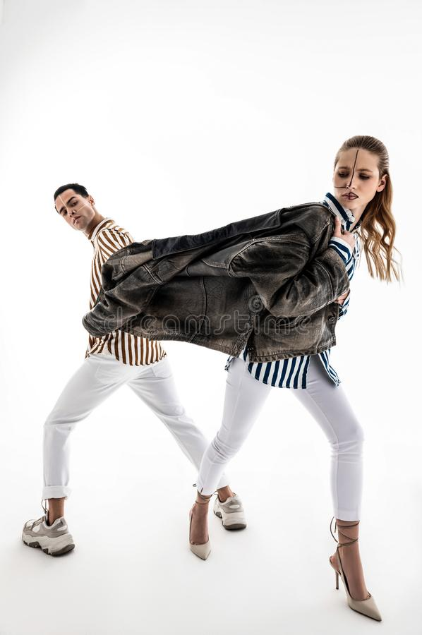 Male and female models wearing white trousers posing in one jacket. Posing in jacket. Male and female models wearing white trousers posing in one jacket working royalty free stock photography