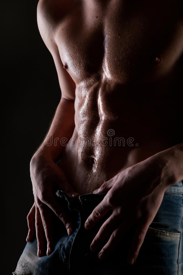 Posing muscular naked man with body in water drops. On black stock image