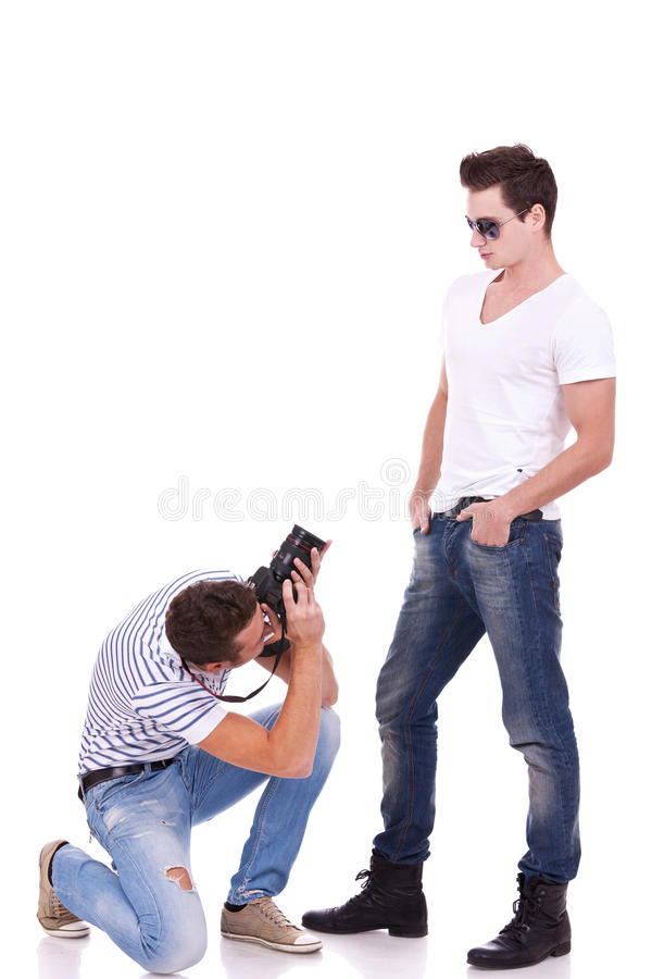 Posing for a professional photographer. Young male fashion model posing for a professional photographer on white background. young men wearing sunglasses being royalty free stock photography