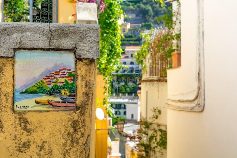 Positano, Italia - 6 de septiembre de 2018 - costa de cerámica colorida tradicional de Amalfi de la placa de calle, Italia fotografía de archivo libre de regalías