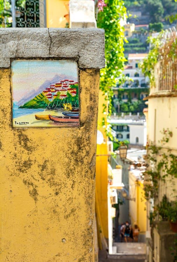 Positano, Italia - 6 de septiembre de 2018 - costa de cerámica colorida tradicional de Amalfi de la placa de calle, Italia - vert foto de archivo libre de regalías