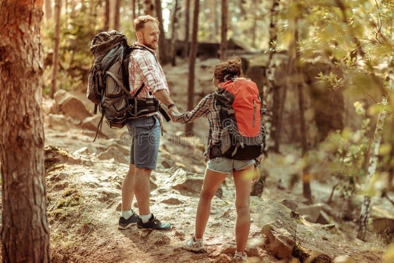 Positief aardig paar die de heuvel samen uitgaan stock afbeelding