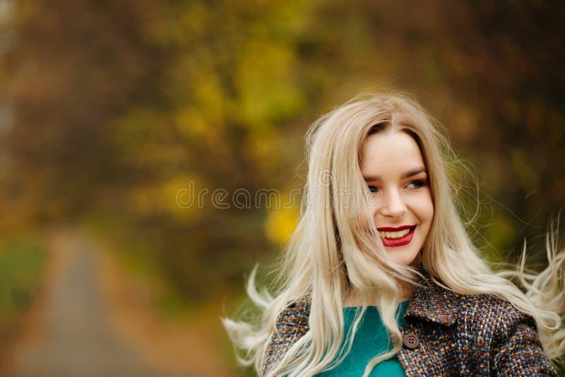 Positief blondemodel in de herfstlaag het stellen dichtbij de gele boom stock fotografie