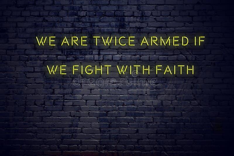 Positief inspirerend citaat op neonteken tegen bakstenen muur worden wij tweemaal bewapend als wij met geloof vechten stock illustratie