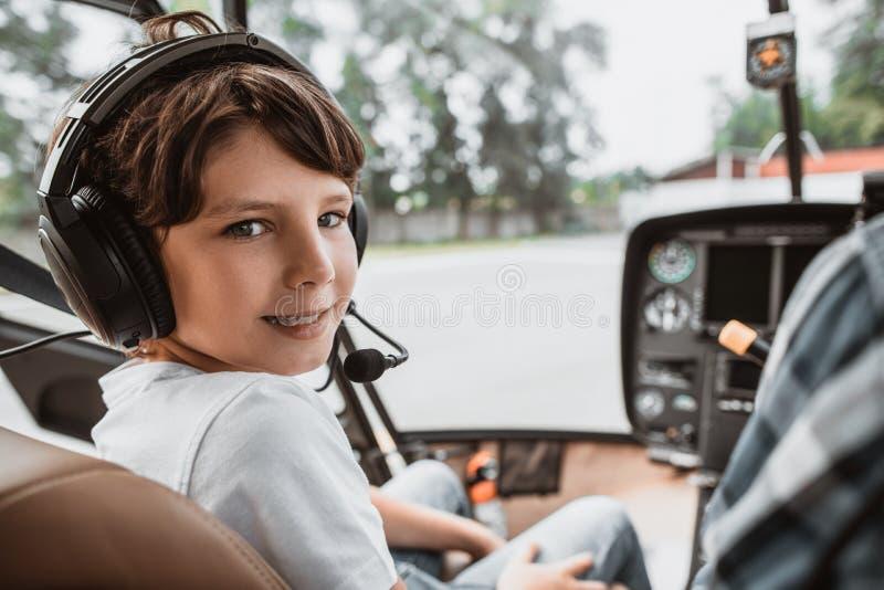Positief jong geitje in hoofdtelefoons die in helikopter onderhouden royalty-vrije stock afbeeldingen