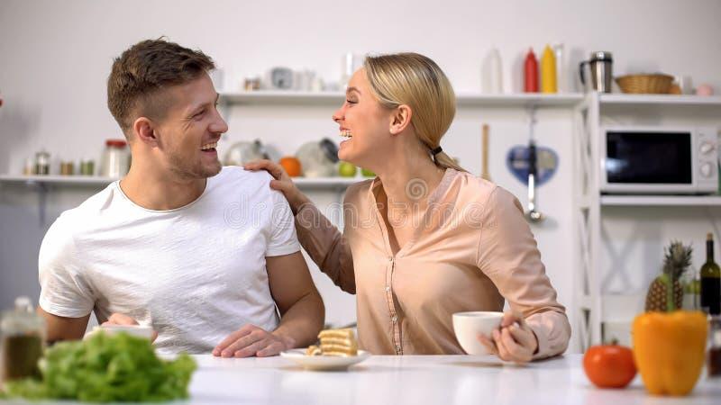 Positief jong paar die zoals hebbend ontbijt, die samen voor de gek houden rond lachen stock afbeeldingen