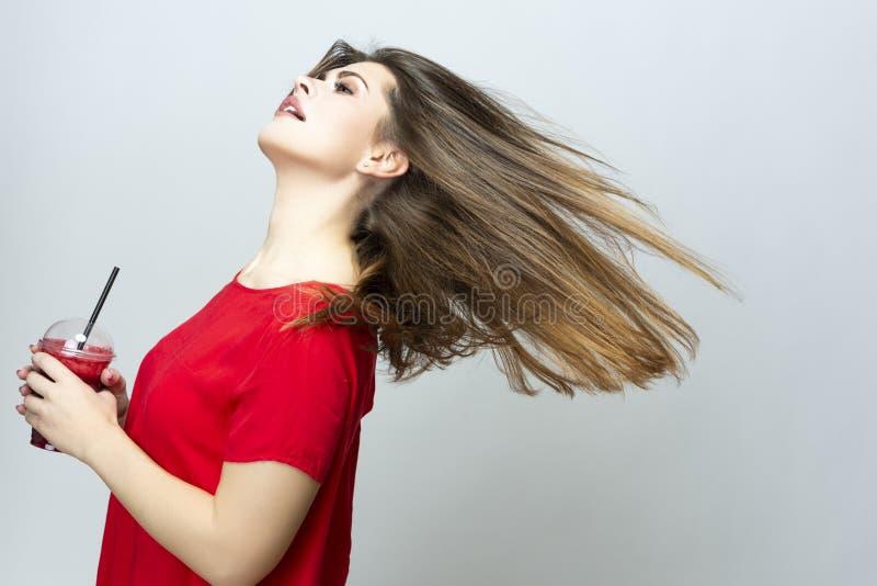 Positief Kaukasisch Wijfje die met Kop van Rode Smoothie Juice Mix dansen Het stellen in rode kleding stock afbeelding