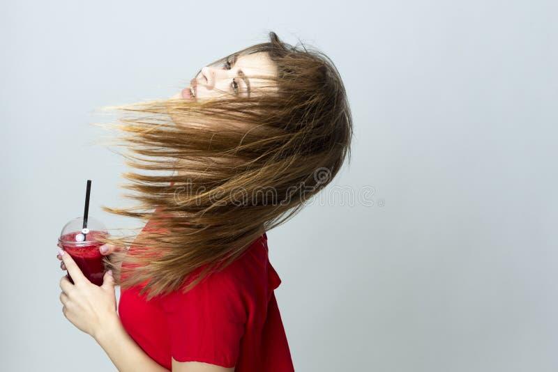 Positief Kaukasisch Wijfje die met Kop van Rode Smoothie Juice Mix dansen Het stellen in Rode Kleding over Wit stock foto