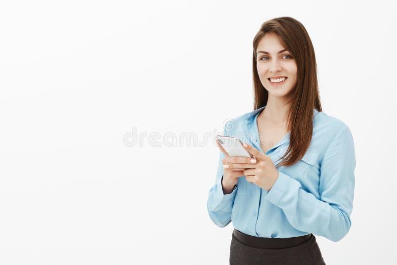 Positief knap brunette in bureaukleren die, die smartphone houden en bij scherm staren die, met groot worden het tevredengesteld stock afbeelding