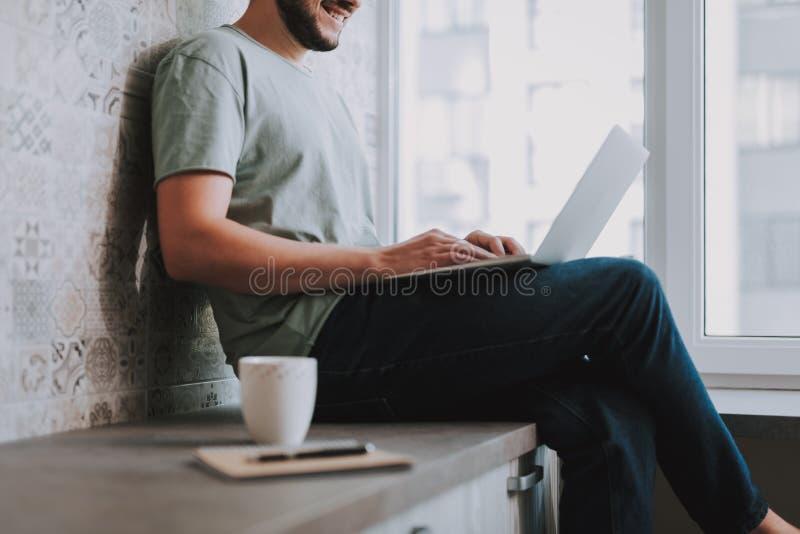 Positief mannetje die freelancer zijn persoonlijke laptop met behulp van stock foto
