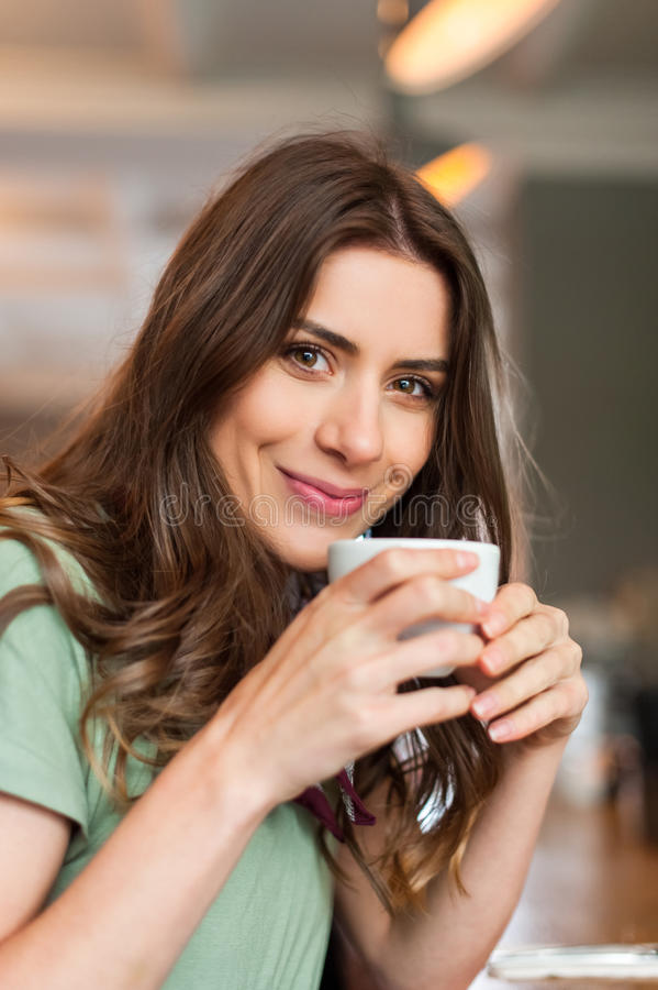 Positief meisje die een onderbrekingszitting nemen bij bar in de koffiewinkel stock foto's