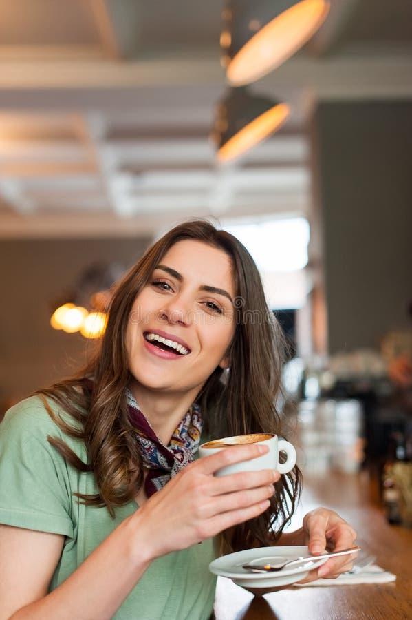 Positief meisje die een onderbrekingszitting nemen bij bar in de koffiewinkel royalty-vrije stock foto's