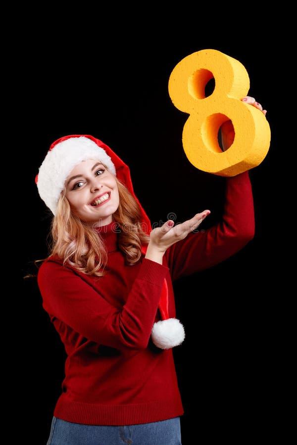 Positief meisje in een kostuum die van de Kerstmiskerstman een aantal acht op een zwarte achtergrond houden het concept van 2018 stock afbeelding