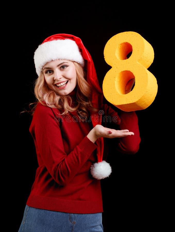 Positief meisje in een kostuum die van de Kerstmiskerstman een aantal acht op een zwarte achtergrond houden het concept van 2018 royalty-vrije stock afbeeldingen