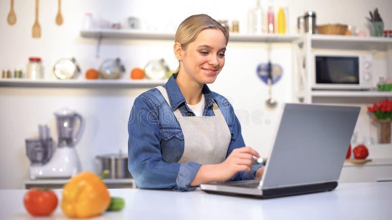 Positief mooi meisje die kokende uiteinden zoeken in Internet, beginner in keuken royalty-vrije stock foto's