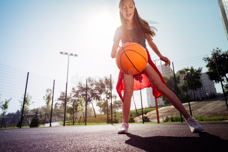 Positief opgetogen longhaired meisjes speel alleen basketbal stock fotografie