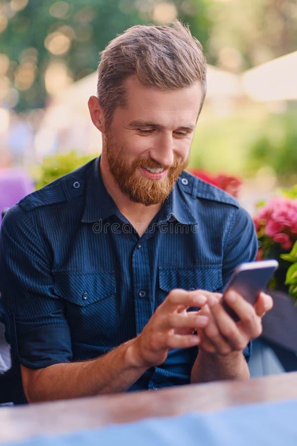 Positief roodharige gebaard mannetje die een smartphone gebruiken stock afbeelding