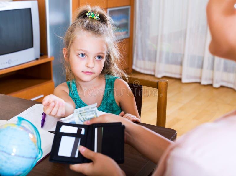 Positief schoolmeisje die geld vragen royalty-vrije stock afbeelding