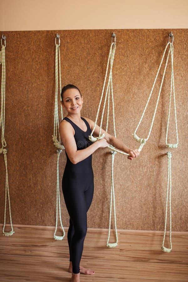 Positief, slank meisje die in sportieve uitrusting de kabels controleren muuryoga royalty-vrije stock foto
