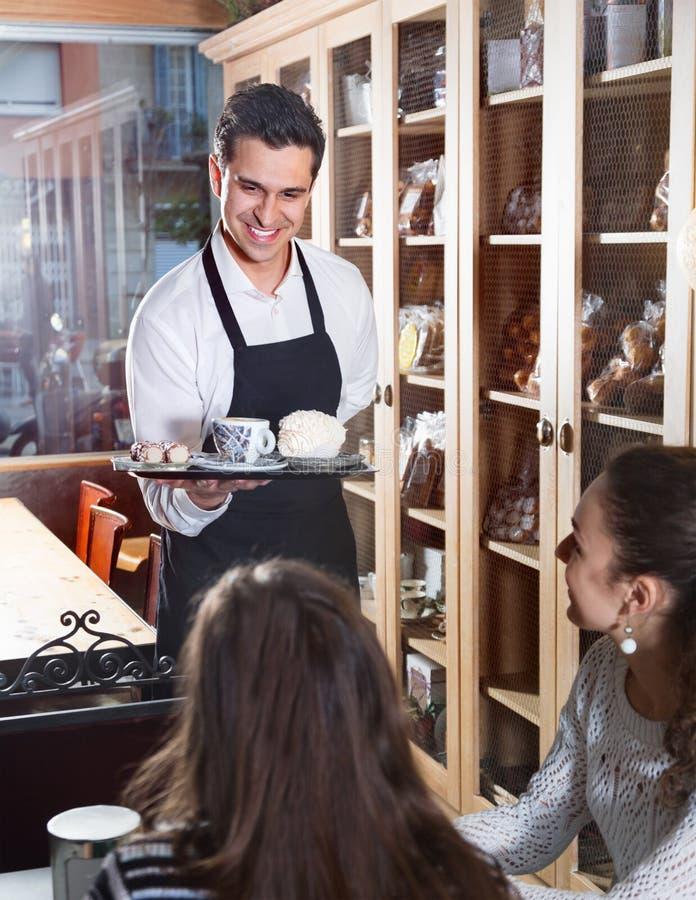 Positief vriendschappelijk serveerster dienend cakes en gebakje voor meisjes royalty-vrije stock afbeelding