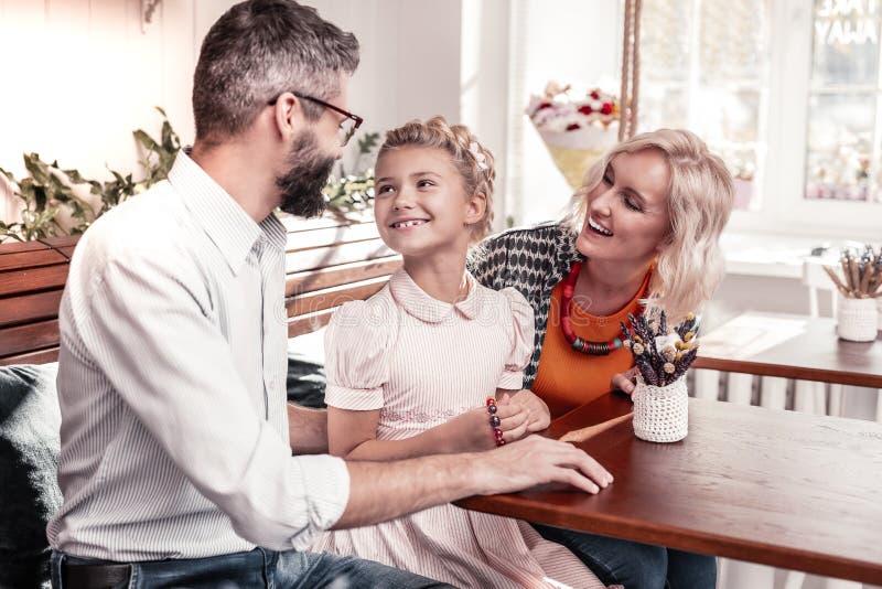 Positief vrolijk meisje die aan haar vader glimlachen stock foto