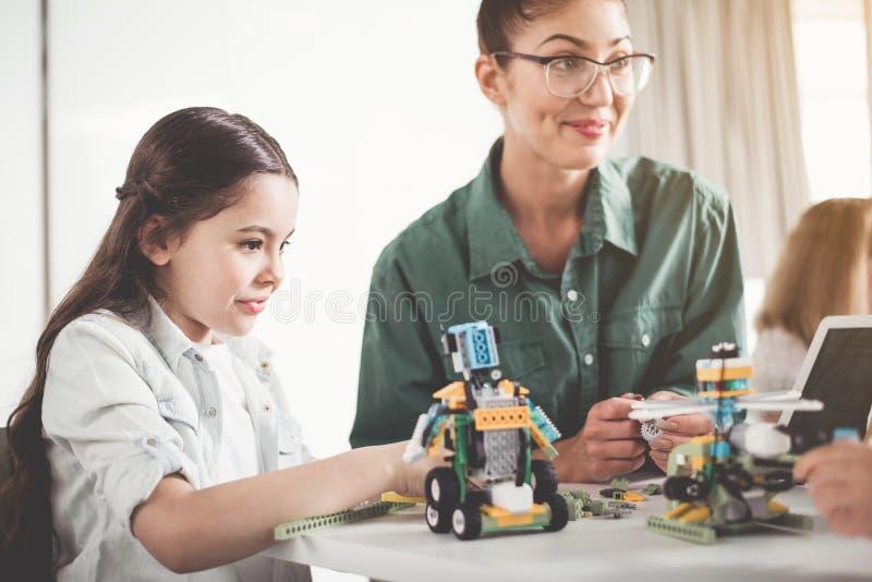 Positief vrouw en jong geitje die elektronisch stuk speelgoed maken royalty-vrije stock afbeelding