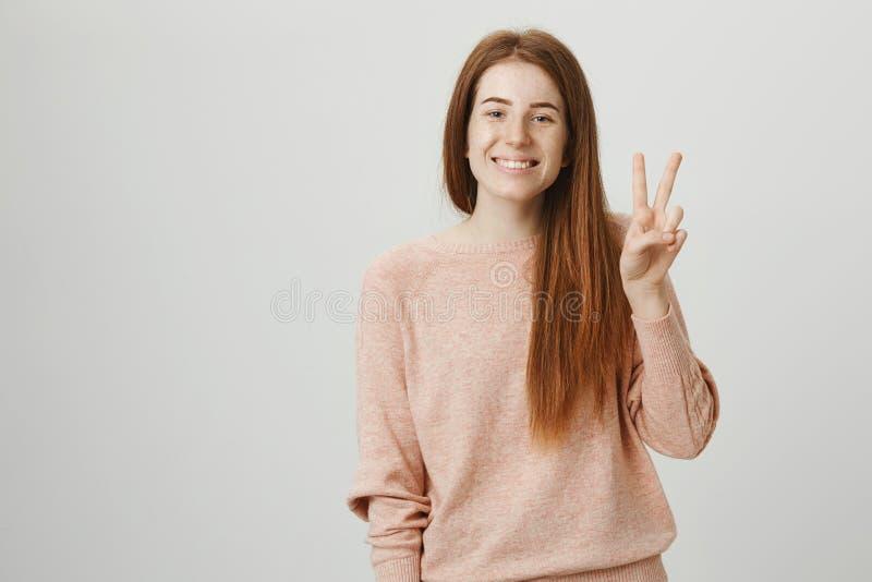 Positieve aantrekkelijke roodharigevrouw die vrede of overwinningsgebaar tonen terwijl ruim het glimlachen, zijnd vriendschappeli royalty-vrije stock foto