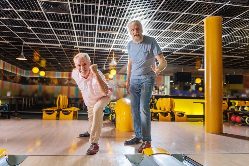 Positieve aardige bejaarden die gelukkig in de kegelenclub voelen stock afbeelding