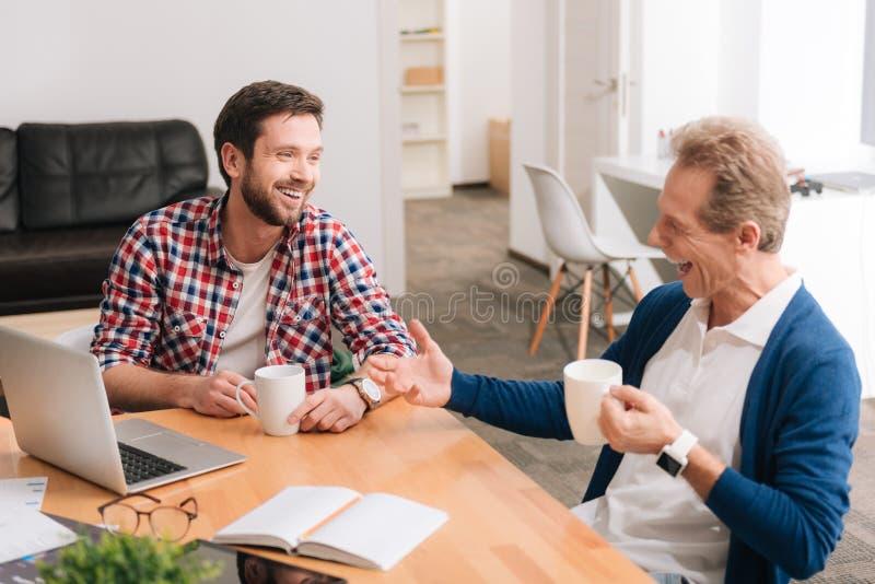 Positieve aardige collega's die koffie drinken stock afbeelding