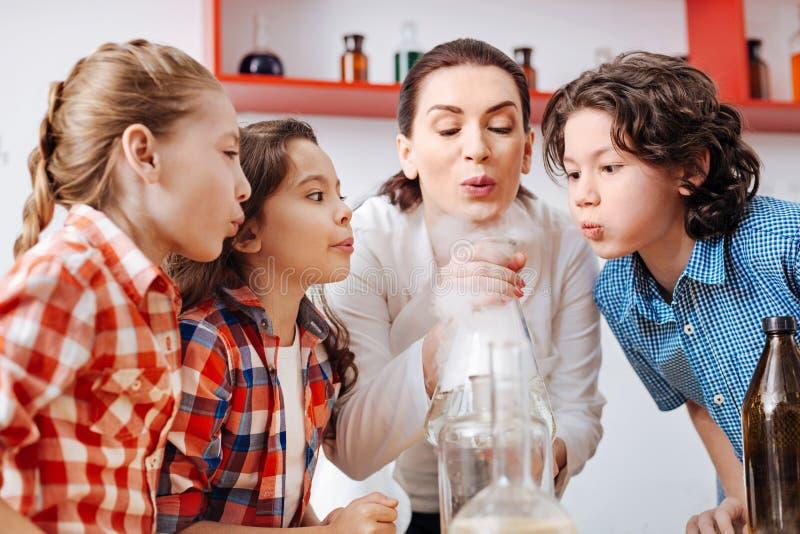 Positieve aardige kinderen die op de chemische fles blazen royalty-vrije stock fotografie
