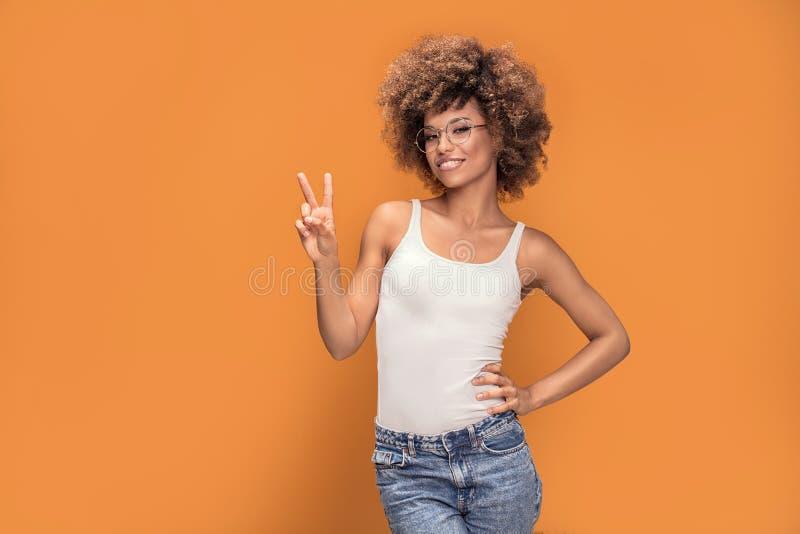 Positieve Afrikaanse Amerikaanse vrouw die vredessymbool tonen stock afbeeldingen