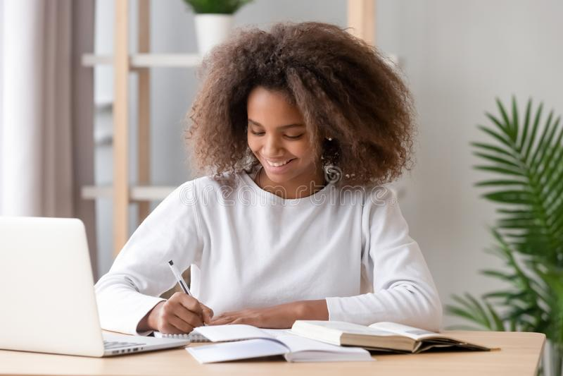 Positieve Afrikaanse schoolmeisjezitting bij bureau en studie stock foto