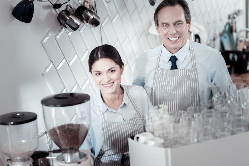 Positieve baristas die en zich dichtbij de koffiemachine glimlachen bevinden stock foto